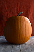A large halloween pumpkin on a wooden surface