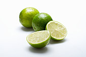 Three limes, one halved, on a white surface