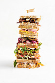 Stacked sandwiches with beef, salmon, cheese, bacon and salad