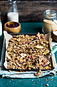 Amaranth and nutbutter granola with dried fruit on a baking tray (vegan)