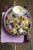 Herring and purple potatoes salad with pickled cucumber and mustard