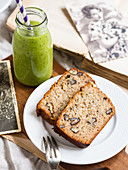 Two slices of flourless (almond and coconut flour) banana bread with nuts, served with green smoothie
