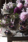 Berry tartlets and flowers on a wooden table