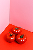 Red tomatoes on a red surface