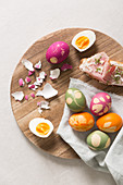 Easter eggs and open ham sandwiches on a wooden plates