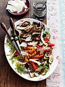 A grilled vegetable platter with parmesan shavings