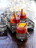 Roter Glühwein mit Zimtstange und Orangen (weihnachtlich)
