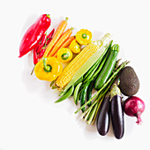 Fresh vegetables arranged by colour on a white background