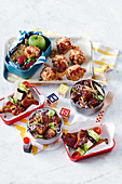 Beany baked potatoes, rainbow noodle salad with meatballs and sticky greek wings