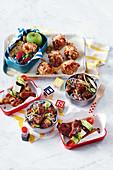 Ofenkartoffeln mit Bohnen, Nudelsalat mit Fleischklösschen, glasierte Hähnchenflügel und griechische Spiesschen