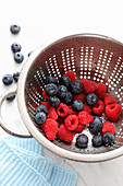 A colander with blueberries and raspberries