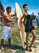 Junge Frau in schwarzem Abendkleid und junger Mann in Badeshorts mit Surfbrett