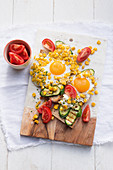 Bread topped with vegetables and fried eggs