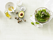 Salad ingredients: lettuce, dressing, avocado and quail eggs