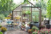 Glashaus mit Sitzplatz und Wasserfaß im Garten