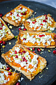 Butternut squash, feta, pistachio and pomegranate seeds tarts