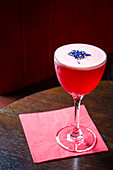 Red cocktail decorated with cornflowers on a red napkin and wooden table