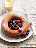 A wreath cake with berries and powdered sugar