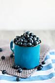 Blueberries in a blue enamel cup