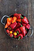 Colourful peppers, chillis and tomatoes in an iron pan