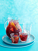 A jug of sangria with several glasses