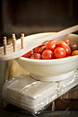 An arrangement of cherry tomatoes, a pasta fork and a pack of pasta