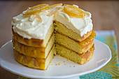 A three-layer lemon cake with frosting and candied lemons