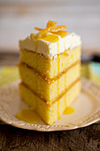 A slice of three-layer lemon cake with frosting