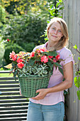 Frau trägt Korb mit Begonia Iconia 'Miss Malibu'