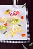 Bunte Gnocchi mit Salbeibutter und Parmesan auf Servierplatte