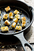 Croutons with herbs on pan