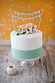 A wedding cake with sugar flowers, a ribbon and a 'Just Married' bunting decoration