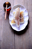 Honigwaben auf Teller, daneben Honigglas mit Honiglöffel