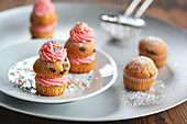 Small muffins with buttercream, icing sugar and sugar sprinkles