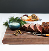 Rolled roast beef with horseradish sauce, rosemary and capers, roast vegetables in the background