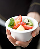Hand holding a small white ball with mixed fruit salad