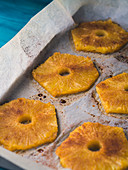 Baked ananas slices with cinnamon, Calvados liqueur and brown sugar on baking tray