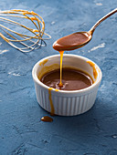 Home made salted caramel in a bowl over blue background