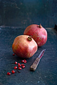 Two pomegranates, pomegranate seeds, and a fruit knife