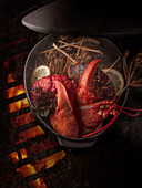 Lobsters with various ingredients in a pot over an open flame grill