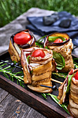 Stuffed aubergine rolls served on a table outdoors