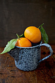 Two oranges in an antique blue enamel jug, sitting on a wooden tabletop