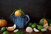 Oranges and limes - peeled, halved and whole - on a wooden table and sitting in an antique blue enamel jug