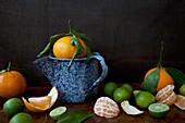 Orangen und Limetten, ganz, geschält und halbiert