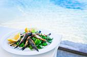 Gegrillte Sardinen mit Zitronen serviert auf Tisch am Pool