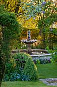 Springbrunnen zwischen Gehölzen und Frühlingsblumen
