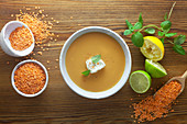 Red lentil soup with ingredients on a wooden surface