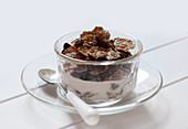 Bowl of Raisin Bran with Milk and Spoon on a White Background