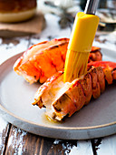 Melting butter on broiled lobster tails