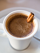 Portuguese coffee served in a cup with a cinnamon stick (close-up)
